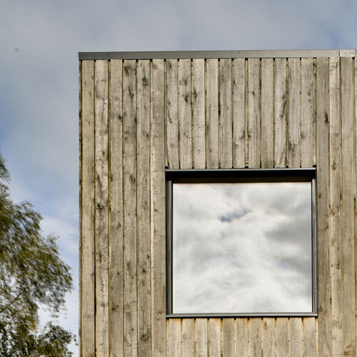 Detail of green oak cladding and aluminium window